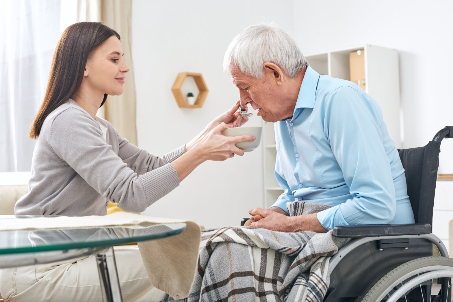 Young Social Worker Holding Bowl With Soup And Spoon By Mouth Of Senior Disable Man Sitting In Wheelchair While Helping Him With Eating 1568x1046